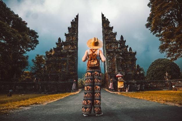 Reizigersvrouw het stellen voor een tempel in bali, indonesië. vrouw met rugzak op een reis in azië