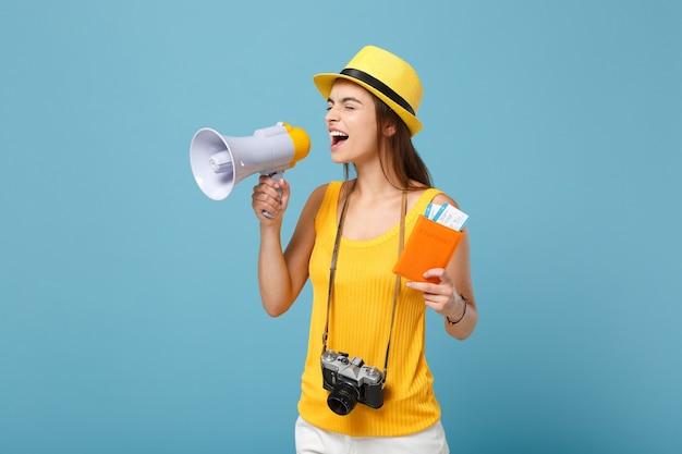 Reizigersvrouw in gele vrijetijdskleding en hoed met kaartjes megafooncamera op blauw