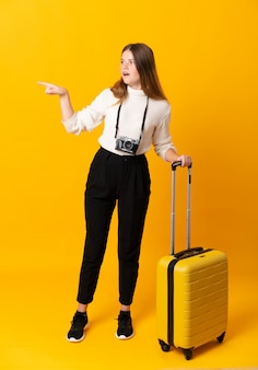Reizigersvrouw met een koffer over geïsoleerde gele achtergrond