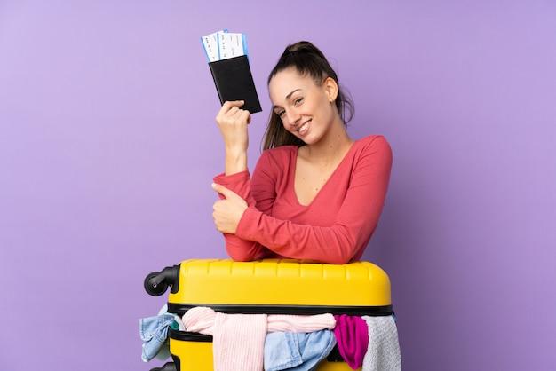 Reizigersvrouw met een kofferhoogtepunt van kleren en het houden van een paspoort over geïsoleerde purpere muur