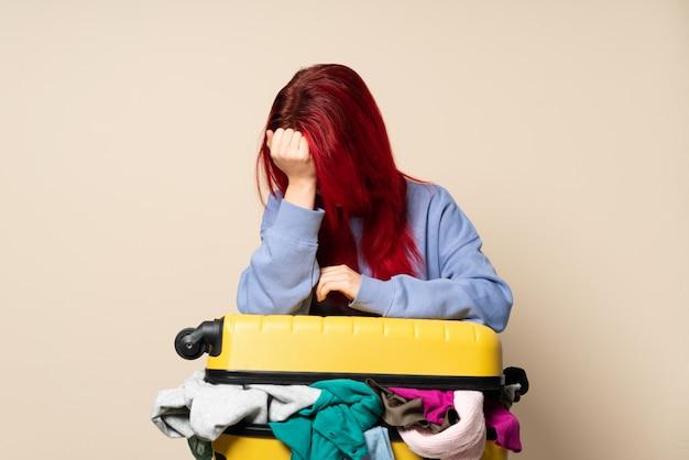 Reizigersvrouw met een kofferhoogtepunt van kleren op beige muur met hoofdpijn wordt geïsoleerd die