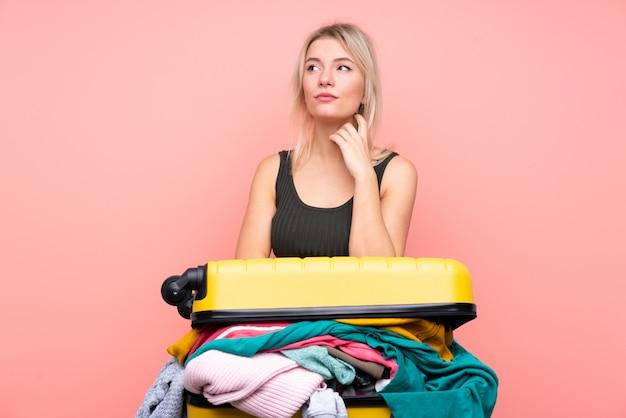 Reizigersvrouw met een kofferhoogtepunt van kleren over geïsoleerde roze muur die een idee denken