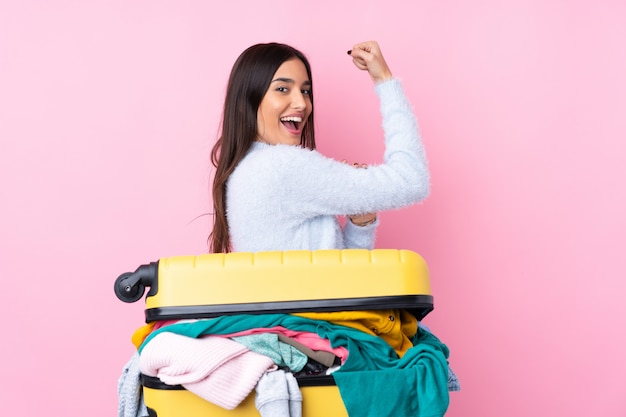 Reizigersvrouw met een kofferhoogtepunt van kleren over geïsoleerde roze muur die sterk gebaar maken