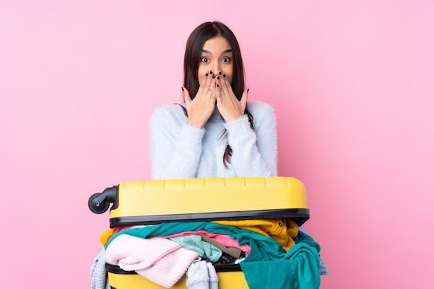 Reizigersvrouw met een kofferhoogtepunt van kleren over geïsoleerde roze muur met verrassingsgelaatsuitdrukking