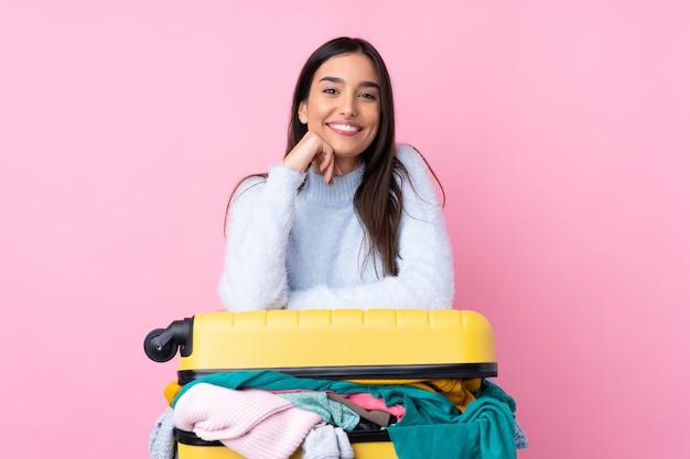 Reizigersvrouw met een kofferhoogtepunt van kleren over geïsoleerde roze muur