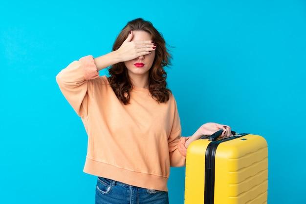 Reizigersvrouw met koffer die ogen behandelen door handen