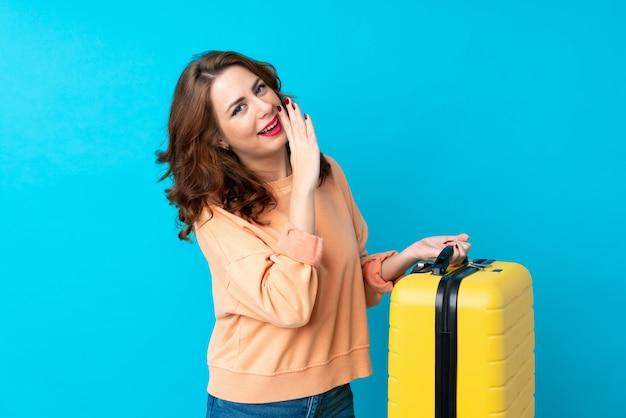Reizigersvrouw met koffer over geïsoleerd fluisterend iets