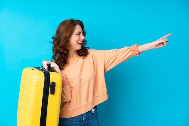 Reizigersvrouw met koffer over geïsoleerde blauwe achtergrond die vinger aan de kant richten
