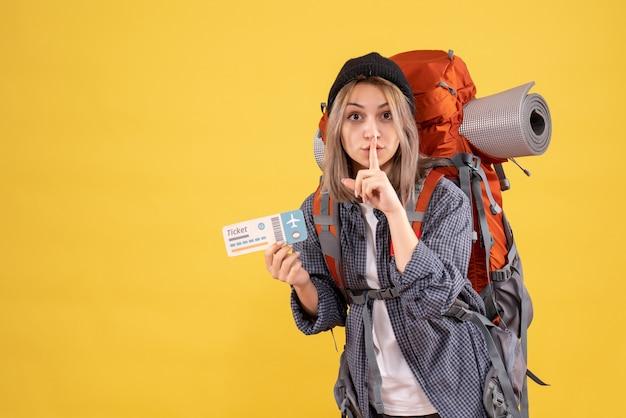 Reizigersvrouw met rugzak die kaartje houdt dat stilteteken maakt