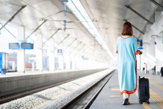 Reizigersvrouwen op platform met bagage en bezittingen in het spoorwegstation.