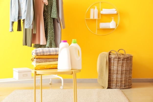 Rek met kleding, wasgoed en wasmiddelen op tafel in de kamer