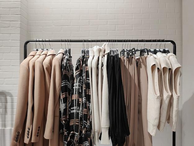 Rek met kleren aan kleerhangers in de winkel tegen de achtergrond van een muur.