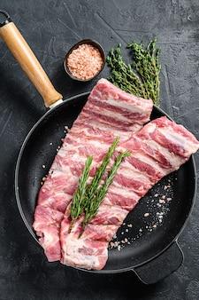 Rek met ongekookt rauw varkensvlees spareribs gekruid met kruiden in een pan. zwarte achtergrond. bovenaanzicht.