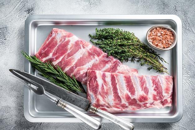 Rek van rauw varkensvlees spareribs in keuken ovenschaal met kruiden