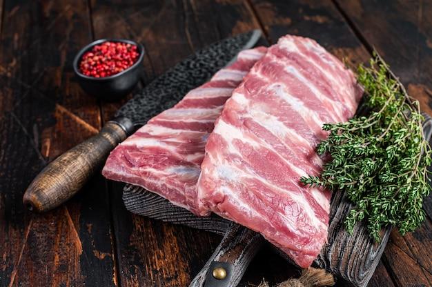 Rek van verse rauwe varkensribbetjes op slager bord. donkere houten achtergrond. bovenaanzicht.