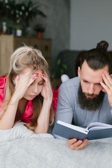Rekeningen te betalen. jong paar dat notitieboekje bekijkt. man en vrouw denken.