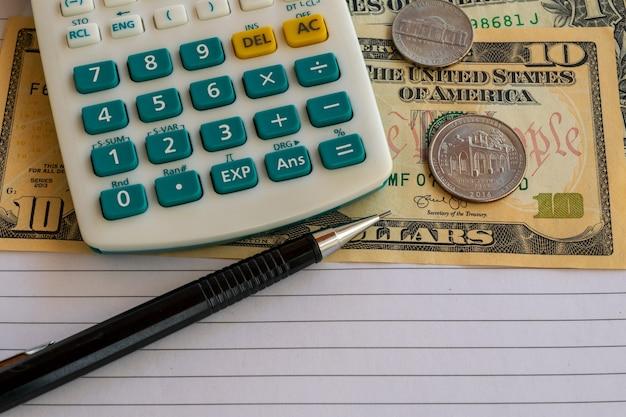 Rekenmachine, amerikaanse dollarbiljetten en valuta op vel papier met mechanisch potlood