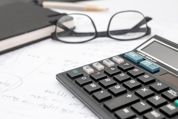 Rekenmachine en documenten voor het werken op de tafel, financiën en besparingen, bedrijfsconcept.
