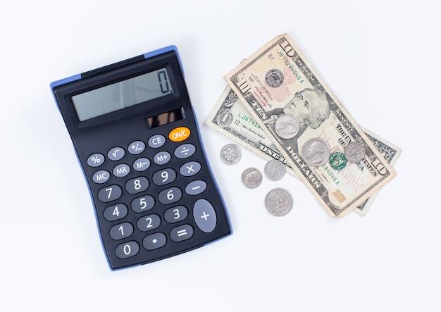 Rekenmachine en dollargeld op witte achtergrond