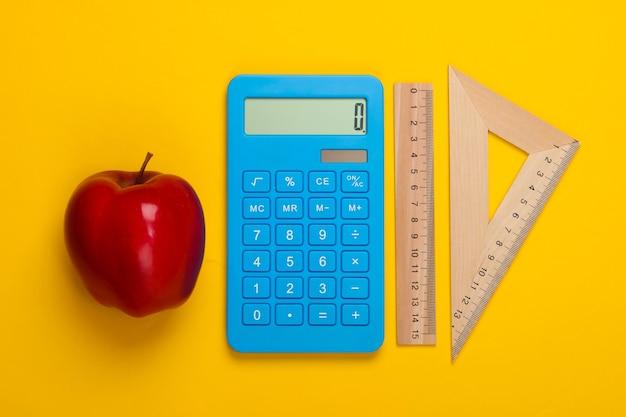 Rekenmachine en houten liniaal, driehoek en appel op geel. onderwijs concept