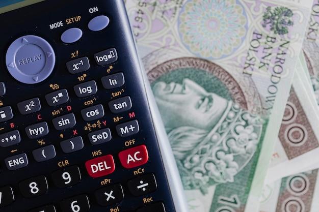 Rekenmachine en poolse zloty-bankbiljetten op een tafel