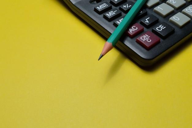Rekenmachine en potlood liggen op een gele achtergrond. detailopname.
