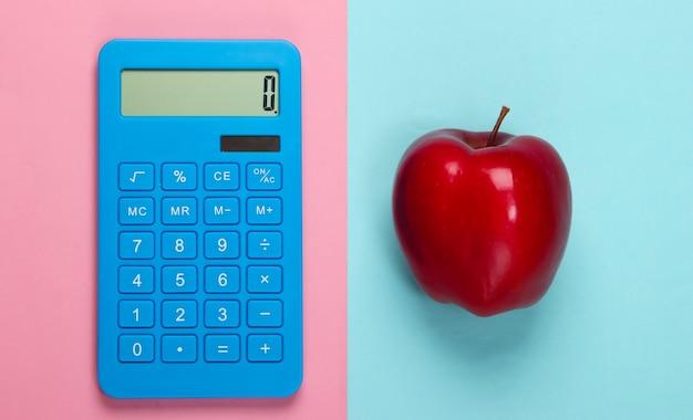 Rekenmachine en rode appel op een bluepinkpastelkleur. onderwijs concept