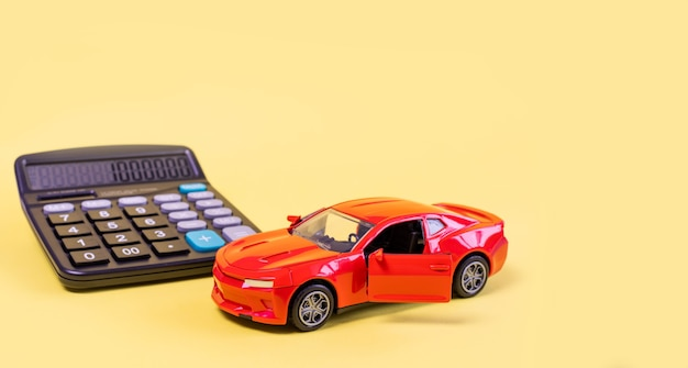 Rekenmachine en speelgoedauto geïsoleerd op gele achtergrond