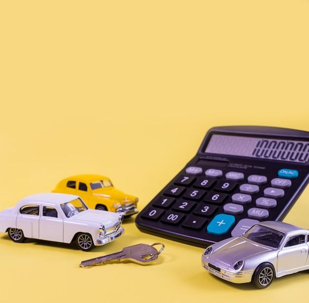 Rekenmachine en speelgoedauto's en sleutels geïsoleerd op gele achtergrond