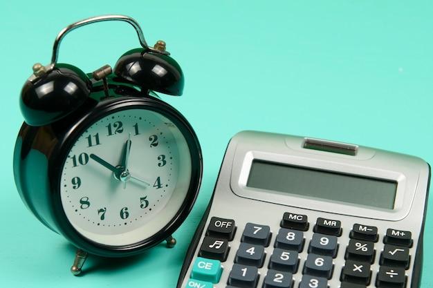 Rekenmachine en wekker op groene achtergrond concept voor tijd is geld voor economie