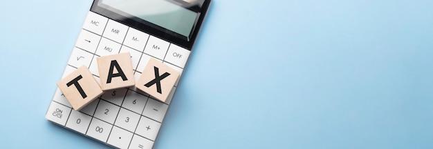 Rekenmachine met belastingwoord op houten blokken
