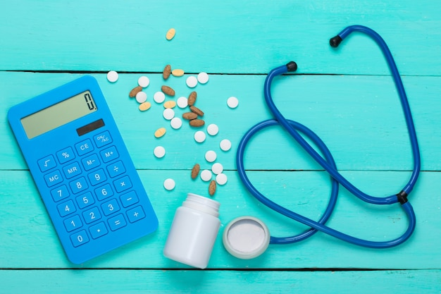 Rekenmachine met fles pillen, stethoscoop op blauwe houten planken