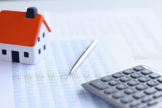 Rekenmachine met kleine huis- en leningdocumenten op tafel om huis te kopen op kredietconcept