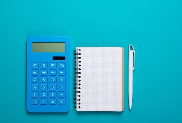 Rekenmachine met notitieboekje op blauwe achtergrond. onderwijsproces. bovenaanzicht. plat leggen