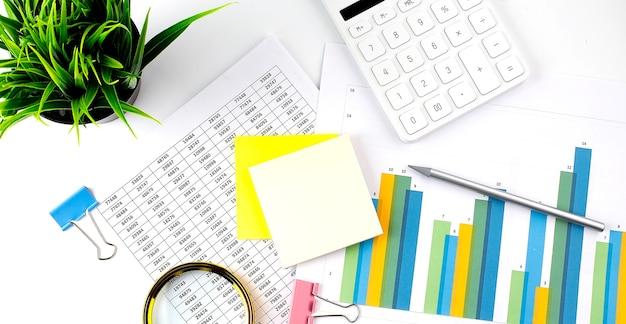 Rekenmachine met pen, sticker op financiële grafiek. concept van zaken en financiën