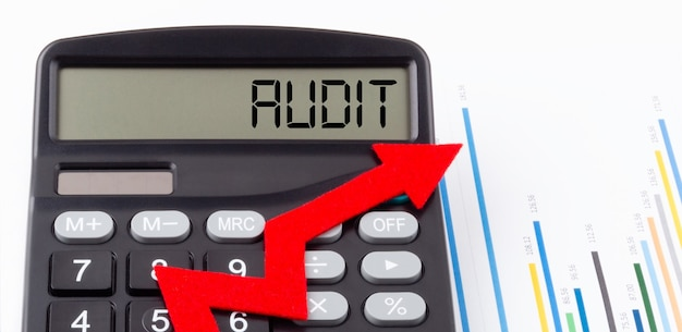 Rekenmachine met rode oplopende pijl en tekst audit op het display, concept