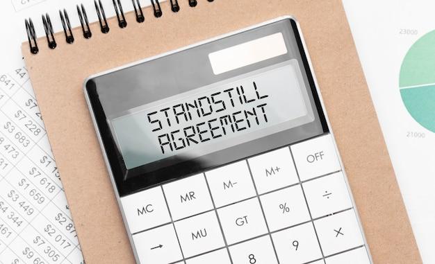 Rekenmachine met tekst stilstandsovereenkomst met ambachtelijke gekleurde notitieblokpen en financiële documenten