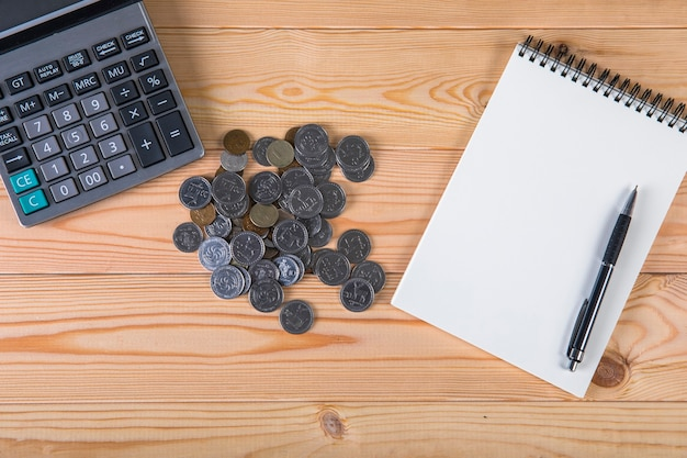 Rekenmachine, munten, blocnote en pen op tafel