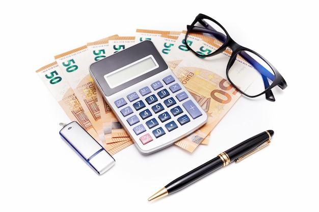 Rekenmachine op bankbiljetten met bril, pendrive en pen op wit