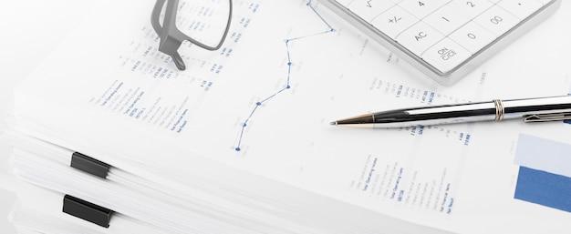Rekenmachine op financiële staat en balans op het bureau van de auditor. concept van boekhoudkundige en auditactiviteiten.