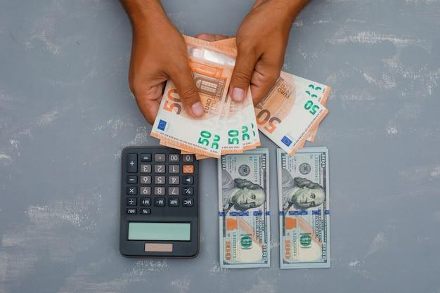 Rekenmachine op gips tafel en man geld tellen.