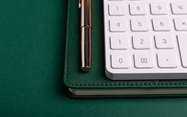 Rekenmachine op groene tafel en notitieboekje met pen. werkplaats van accountant.