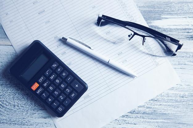 Rekenmachine, papieren, glazen en pen op tafel. desktopconcept