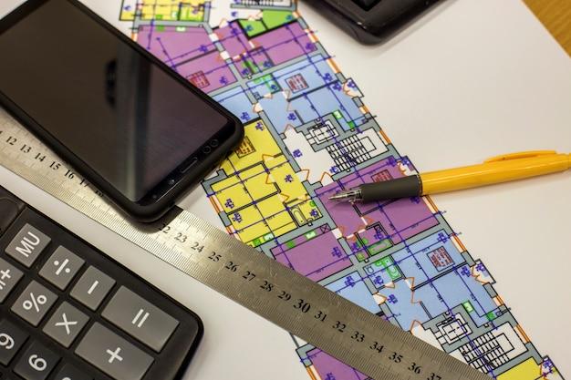 Rekenmachine, pen en liniaal bij het bouwen van huisarchitectuur plan tekening blauwdruk. planning, meting en investeringen.
