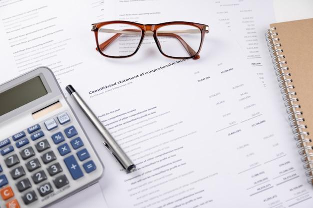 Rekenmachine, pen, notitieboekje en financieel verslag zet op de witte tafel boekhoudkundige concepten.bovenaanzicht