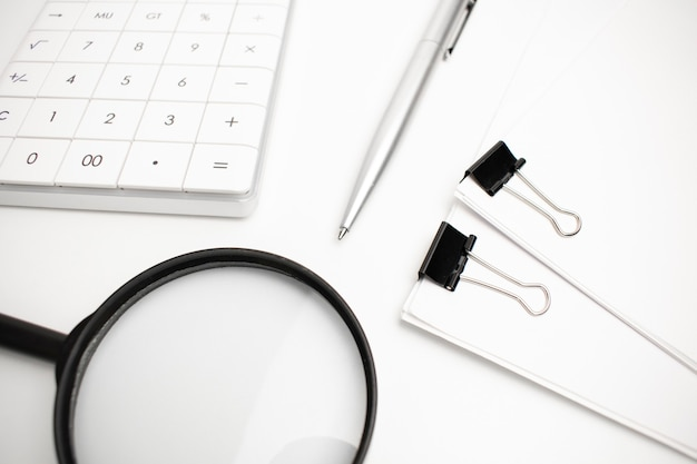 Rekenmachine, pen, wit papier voor notities liggen op het oppervlak van een houten tafel