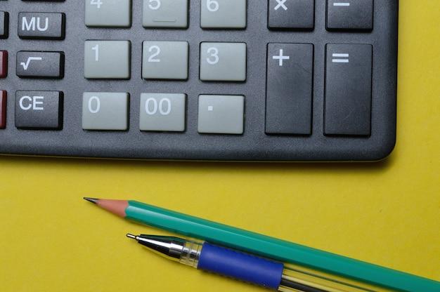 Rekenmachine potlood en pen op een gele achtergrond. detailopname.