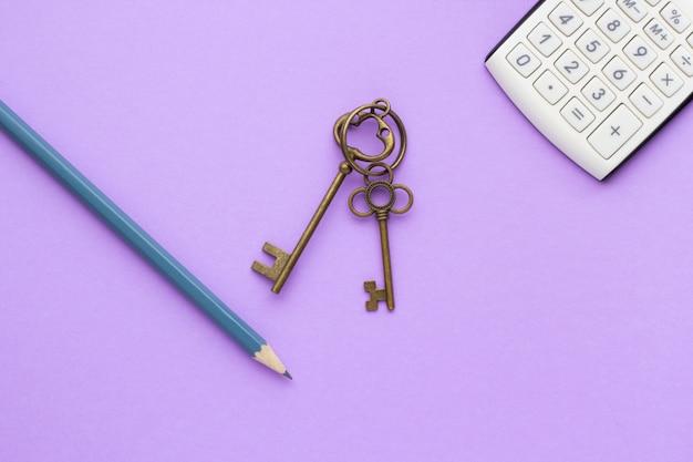 Rekenmachine, sleutels en potlood op een lila tafel