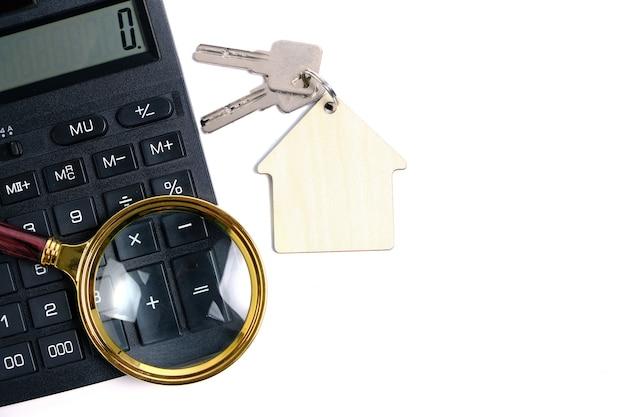 Rekenmachine, vergrootglas en huissleutels. concept van het kopen en verkopen van woningen, hypotheken en het huren van een huis of appartement.