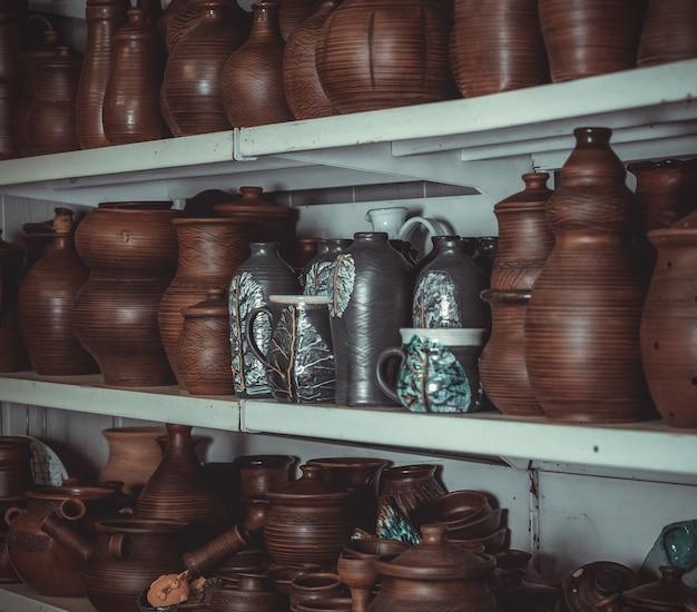 Rekken in een pottenbakkerij met aardewerk, veel verschillende soorten aardewerk staan op de planken